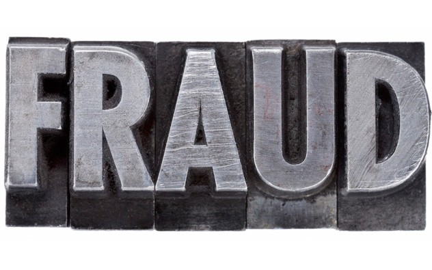 Typewriter letters that spell the word fraud