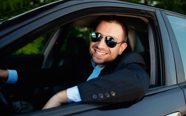 A man in business attire driving