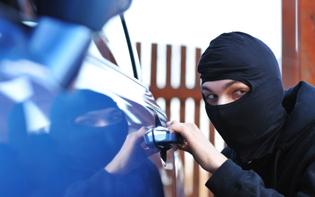 A masked thief breaking into a car